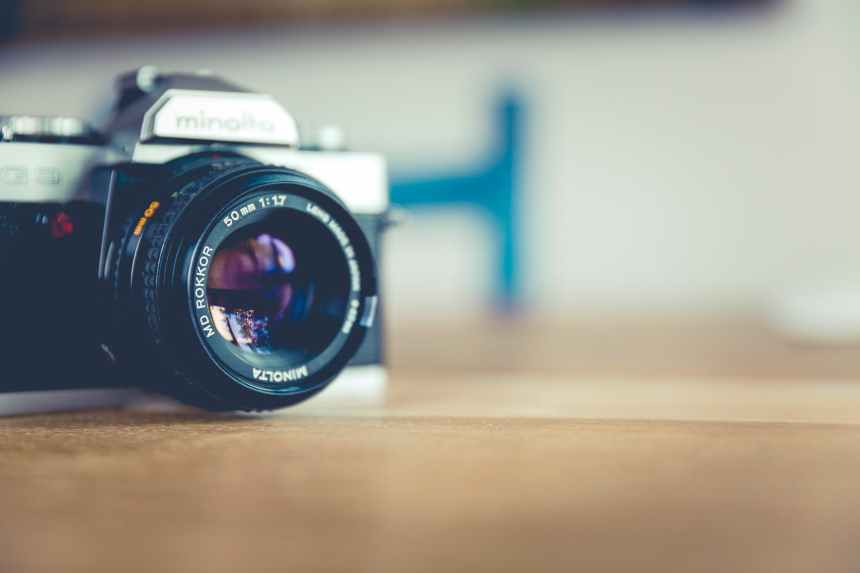 shallow focus photo of dslr camera on brown wooden table